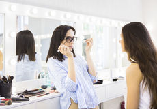 Young makeup artist doing makeover to pretty model Stock Image
