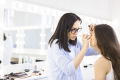 Young makeup artist doing makeover to pretty model. At beauty salon Stock Photography