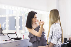 Young makeup artist doing makeover to pretty model Royalty Free Stock Photography