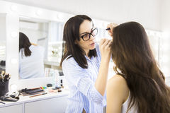 Young makeup artist doing makeover to pretty model Royalty Free Stock Photos