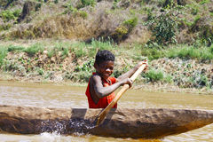 Young Malagasy african boy rowing traditional canoe Royalty Free Stock Photography