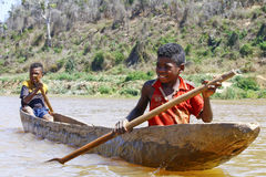 Young Malagasy african boy rowing traditional canoe Stock Photography