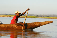 Young Malagasy african boy rowing traditional canoe on river Stock Photos