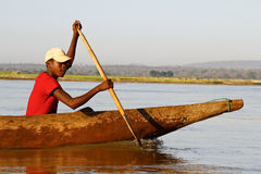 Young Malagasy african boy rowing traditional canoe on river Stock Photo