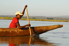 Young Malagasy african boy rowing traditional canoe on river Stock Photography