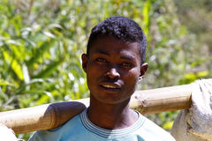 Young Malagasy man carrying sacks of rice on bamboo stick. African poverty Stock Photography