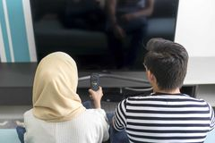 Young Malay Couple at the Sofa watching tv together. People, couch, adult, television, woman, leisure, home, entertainment, sitting, indoors, lifestyle, room stock photos