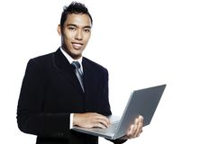 Young malay entrepreneur with laptop computer. Young smiling malay entrepreneur businessman wearing business suit and giving a presentation with his laptop Royalty Free Stock Photo