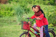 A young malay female children ride a bicycle at their hometown. Smile face from them. View a background of Malay rural village. royalty free stock photo