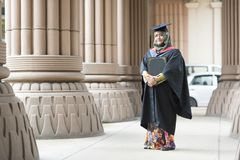 Young Malaysian woman holding a degree certificate while smiling on her graduation day. Education concept - young woman holding a degree certificate while Royalty Free Stock Photography