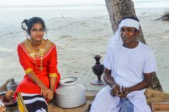 Young maldivian couple dressed in national clothes cooking breakfast royalty free stock photos