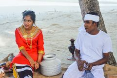 Young maldivian couple dressed in national clothes cooking lunch stock image