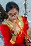 Young maldivian girl in national clothes smoking shisha. In Maldives stock images