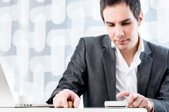 Young male accountant calculating earnings and profit Stock Photo