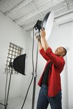 Young male adjusting studio lights. royalty free stock images