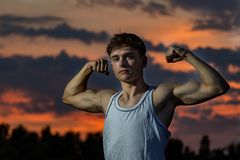 Young adult male outside at sunset. Young male adult flexing his arm  muscles at sunset Stock Photos