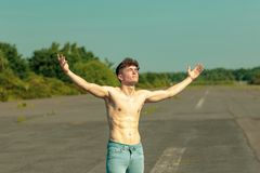 Young adult male shirtless outdoors. Young male adult with his arms out enjoying the sunshine shirtless on a warm summer`s day Stock Photography