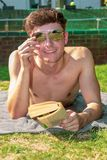 Young male adult laying in the sun reading a book. In the summer weather Stock Photos