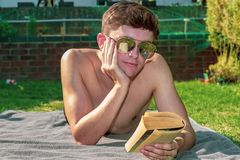Young male adult laying in the sun reading a book. In the summer weather Royalty Free Stock Images