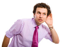 Young male adult listening carefully, spying. Young attractive male adult, pink shirt and tie listening carefully, spying, all isolated on white background stock photography