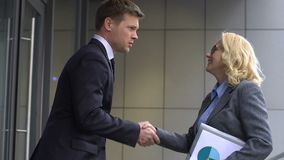 Young male applicant greeting HR employee, hurrying to office for job interview