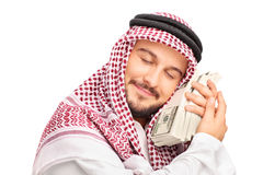 Young male Arab person sleeping on money stock image
