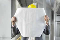Young male architect analyzing blueprint in industry Royalty Free Stock Photography