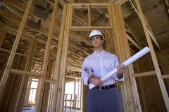 Young male architect with blueprint in partially built house, smiling, portrait, low angle view Stock Images