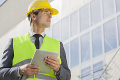 Young male architect with digital tablet looking away outside building Stock Images