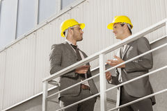 Young male architect discussing on stairway against building Royalty Free Stock Images