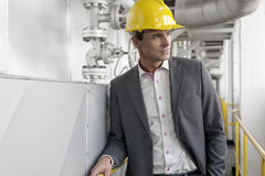 Young male architect in hard hat looking away at industry Stock Photos