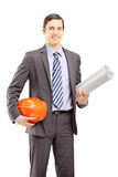 Young male architect holding blueprints and helmet Royalty Free Stock Photography