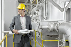 Young male architect holding rolled up blueprints by industrial machinery Stock Photos