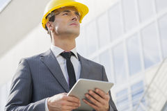 Young male architect holding tablet PC against building Royalty Free Stock Photography
