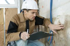 Young male architect inspecting wall at construction site. Young Stock Photography