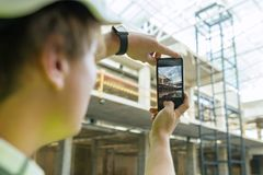 Young male architect photographs a construction site. Building, development, teamwork and people concept.  Royalty Free Stock Images