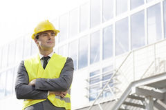 Young male architect in protective wear standing arms crossed outside building Stock Images