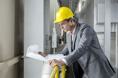 Young male architect reading blueprint while leaning on railing in industry Stock Photos