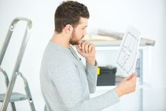 Young male architect reading blueprint. Young Stock Photography