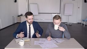Young male architect is showing the project to his boss in modern conference room. Professionals are sitting at the wooden table in the office and engineer is stock footage