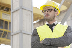 Young male architect standing arms crossed at construction site Stock Photo