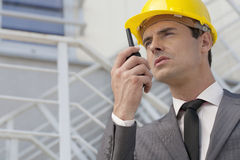 Young male architect talking on two-way radio against building stock photo