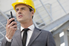 Young male architect talking on two-way radio outdoors Royalty Free Stock Images