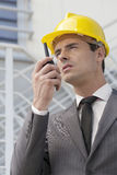 Young male architect talking on walkie-talkie against building Royalty Free Stock Photography