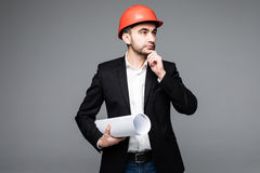 Young male architect wearing helmet and holding blueprints Royalty Free Stock Photography