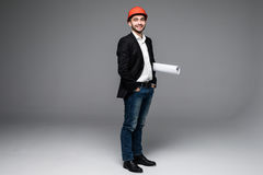 Young male architect wearing helmet and holding blueprints Royalty Free Stock Photos