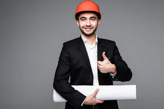 Young male architect wearing helmet and holding blueprints Stock Images