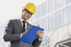 Young male architect writing on clipboard against office building Royalty Free Stock Images