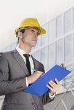 Young male architect writing on clipboard while looking away outside office building Stock Images