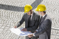 Young male architects analyzing blueprint at construction site Royalty Free Stock Photo